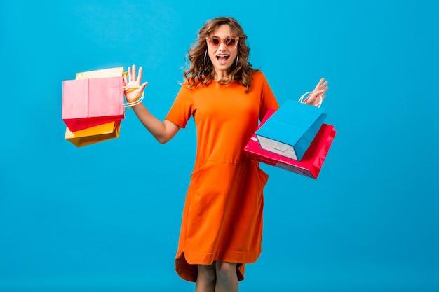 Attraktive glückliche lächelnde stilvolle frau shopaholic in orange trendigem übergroßem kleid, das das laufen hält, das einkaufstaschen auf blauem hintergrund lokalisiert hält