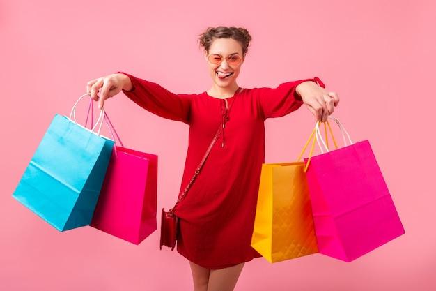 Attraktive glückliche lustige emotion stilvolle frau shopaholic im roten trendigen kleid, das bunte einkaufstaschen auf rosa wand lokalisiert, verkauf aufgeregt, frühlingssommer-modetrend hält