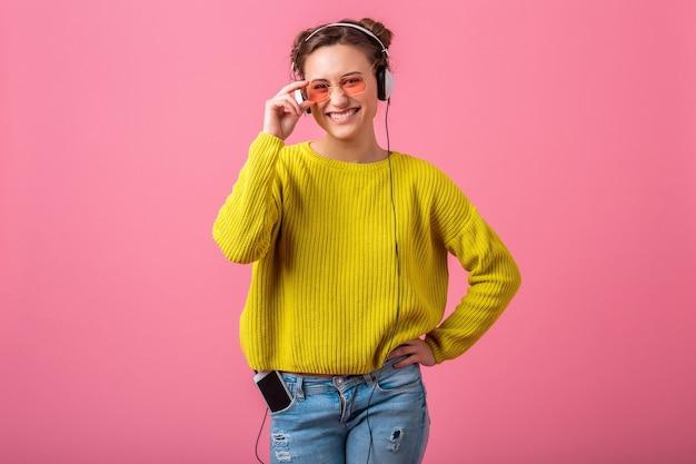 Attraktive glückliche lustige frau, die musik in kopfhörern gehört, gekleidet in buntem hipster-stil-outfit lokalisiert auf rosa wand, tragenden gelben pullover und sonnenbrille, spaß habend
