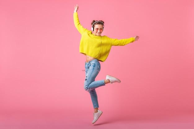 Attraktive glückliche lustige frau, die springend hört musik in kopfhörern gekleidet in buntem hipster-stil-outfit lokalisiert auf rosa wand, tragenden gelben pullover und sonnenbrille, spaß habend