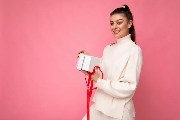 Attraktive glückliche positive lächelnde junge brünette frau lokalisiert über rosafarbener hintergrundwand, die weißen pullover mit geschenkbox hält und geschenk auspackt, der die kamera betrachtet. platz kopieren, mockup