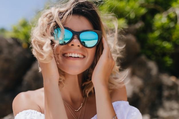 Attraktive glückselige frau, die lacht, während sie auf natur aufwirft. nahaufnahme-außenporträt der reizenden frau mit kurzen hellen haaren.