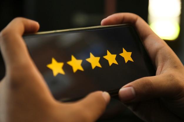 Attraktive hände, die fünf-sterne-bewertung auf einem smartphone geben