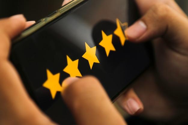 Attraktive hände, die vier-punkte-fünf-sterne-bewertung auf einem smartphone geben