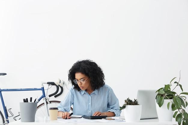 Attraktive hausfrau mit gemischten rassen, die konzentriert aussieht, während sie zu hause rechnungen berechnet