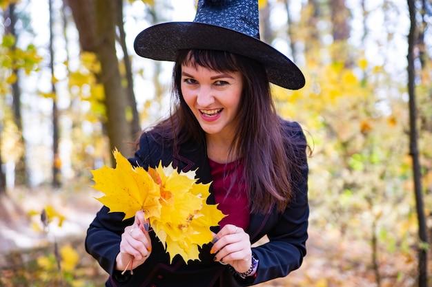 Attraktive hexe in den herbstlichen wald zaubert. gelbe abgefallene ahornblätter im hintergrund