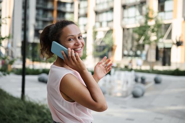 Attraktive hispanische junge frau, die am handy spricht, süß mit einem zahnigen lächeln lächelt, während sie die kamera betrachtet und auf dem hintergrund der städtischen gebäude steht. kommunikations- und geschäftskonzept