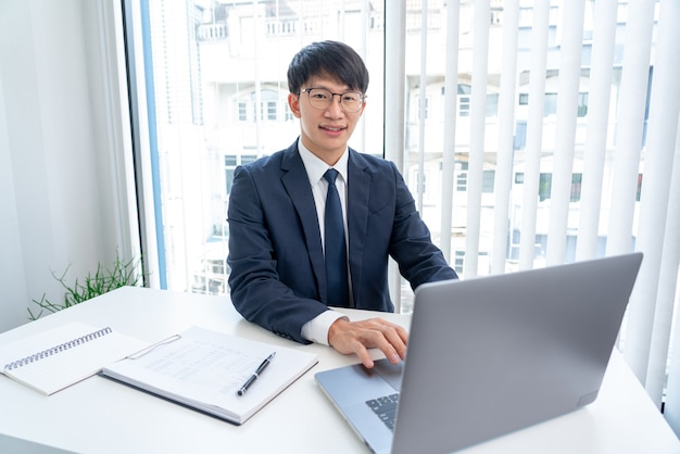 Attraktive hübsche asiatische geschäftsleute in den gläsern, die positiv glücklich lächeln