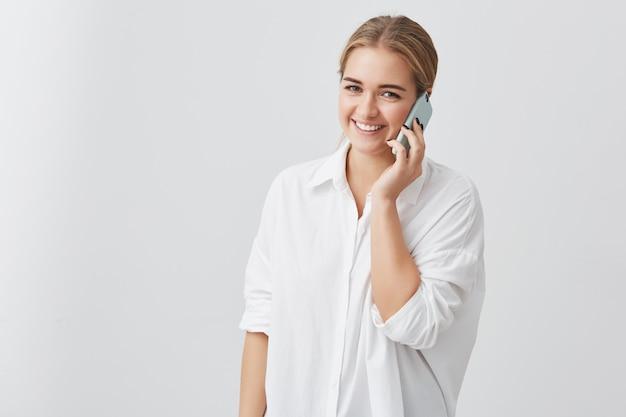Attraktive hübsche blonde frau, die weißes hemd trägt, das anmutiges und glückliches aussehen beim sprechen über smartphone mit ihrem geliebten hat. menschen- und technologiekonzept