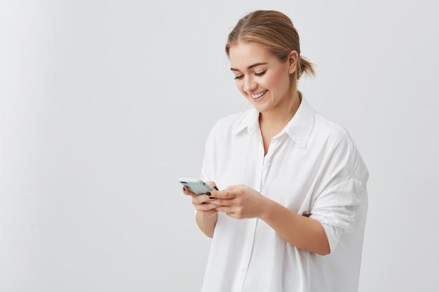 Attraktive hübsche frau mit blondem haar im weißen hemd, das lächelt, während handy benutzt, das mit ihrem freund aufwirft, der aufwirft. schönheits- und jugendkonzept