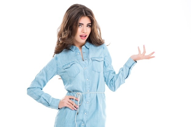 Attraktive hübsche junge frau in blauem freizeitkleid, die exemplar auf der handfläche isoliert über weißer wand hält