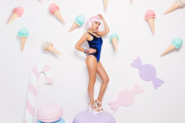 Attraktive hübsche sexy junge frau im bodysuit mit geschnittener rosa frisur, auf den fersen stehend auf riesigem macaron unter süßigkeiten. pastellfarben, genießen, süßer lebensstil.