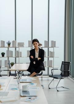 Attraktive intelligente geschäftsfrau, die im modernen büroraum selbstbewusst sitzt. professioneller finanzarbeiter. berufstätige frau im anzug. weibliche führung.