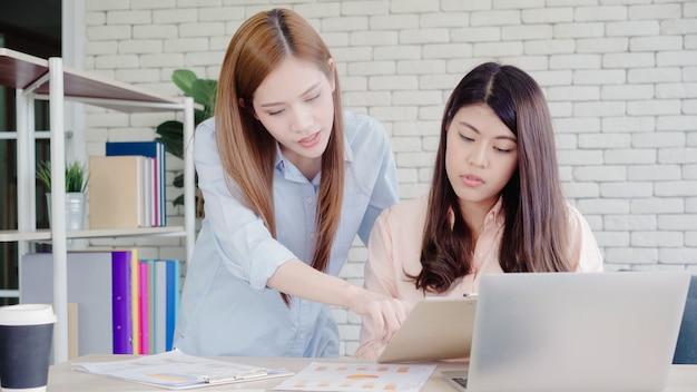 Attraktive intelligente kreative asiatische geschäftsfrauen in der intelligenten freizeitkleidung, die an laptop beim sitzen arbeitet