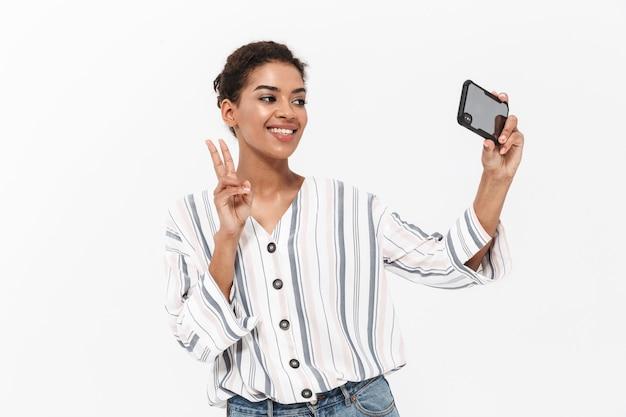 Attraktive junge afrikanerin in freizeitkleidung, die isoliert über weißer wand steht, ein selfie macht und frieden zeigt