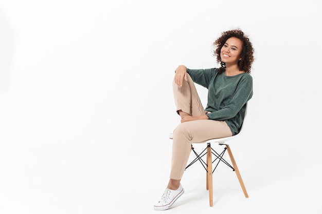 Attraktive junge afrikanerin sitzt auf einem stuhl isoliert über weißer wand und posiert