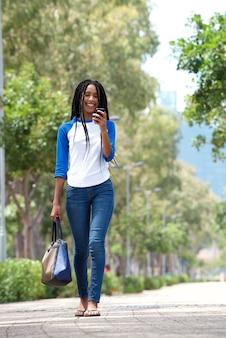 Attraktive junge afrikanische frau des vollen körpers, die draußen in die stadt unter verwendung des mobiltelefons geht