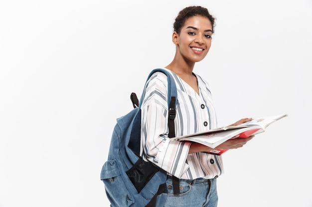 Attraktive junge afrikanische frau in freizeitkleidung, die isoliert über weißer wand steht, rucksack trägt und lehrbuch hält
