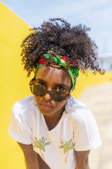 Attraktive junge afroamerikanerin mit sonnenbrille und stirnband