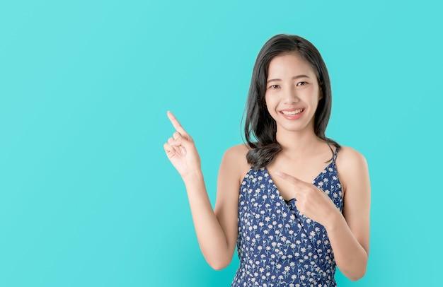 Attraktive junge asiatische frau, die den finger zeigend steht und fühlen sich glücklich