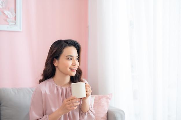 Attraktive junge asiatische frau, die kaffee beim sitzen auf sofa trinkt.