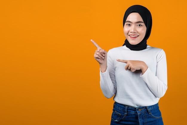 Attraktive junge asiatische frau, die lächelt und auf leeren raum zeigt