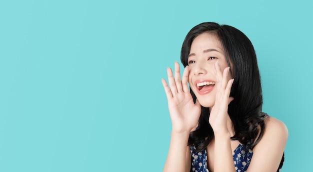 Attraktive junge asiatische frau, die mit den händen zum mund ankündigt und ein geheimnis erklärt.