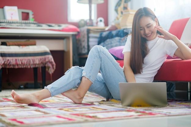 Attraktive junge asiatische frau, die zu hause arbeitet.