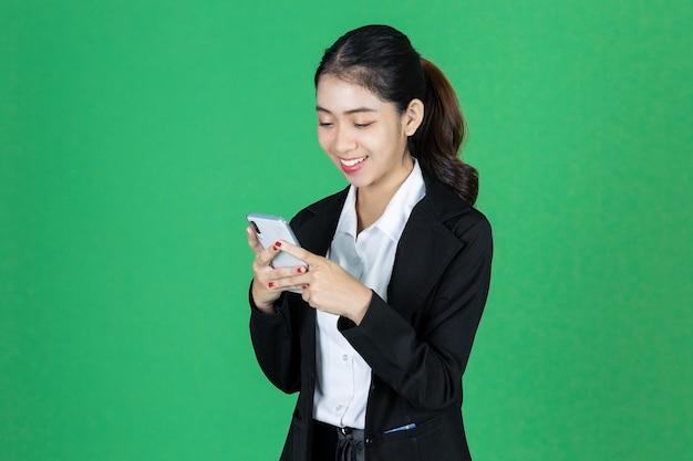 Attraktive junge asiatische geschäftsfrau mit dem mobilen smartphone in den händen