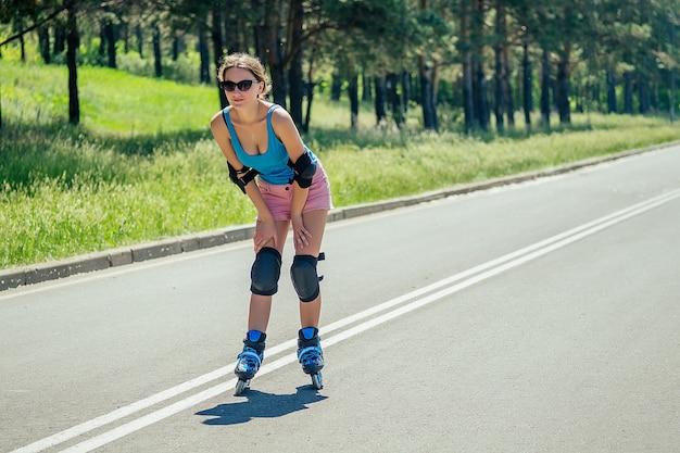 Attraktive junge athletische schlanke brünette frau in rosa shorts und blauem oberteil mit ellbogenschützern und knieschützern reitet auf rollschuhen im park