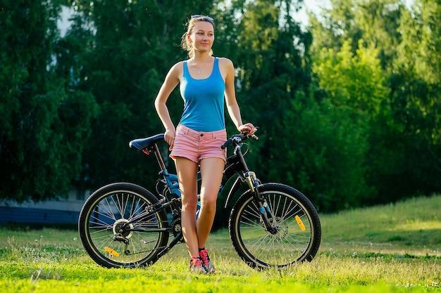 Attraktive junge athletische schlanke brünette frau in rosa shorts und blauem top auf dem fahrrad im park