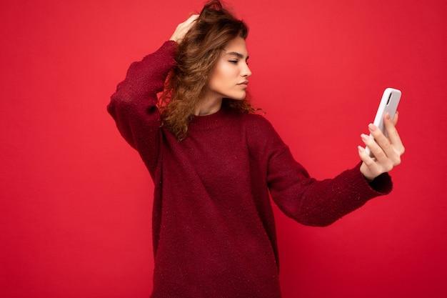 Attraktive junge blogger-frau mit lockigem haar, die einen dunkelroten pullover trägt, der auf rotem hintergrund isoliert ist und ein smartphone mit blick auf den telefonbildschirm und selfie hält.
