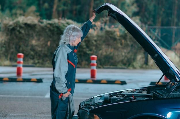 Attraktive junge blonde frau, die eine automechanikeruniform trägt und das auto repariert