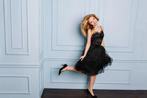 Attraktive junge blonde frau, die spaß hat, tanzt, springt und ein bein hochhält. sie lächelt, trägt ein schwarzes, stilvolles kleid und high heels.