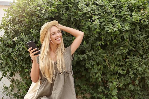 Attraktive junge blonde frau, die über grünem garten am sonnigen hellen tag mit handy in der hand aufwirft, romantisches leinenkleid und strohhut tragend