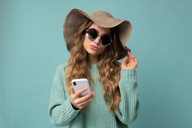 Attraktive junge blonde frau mit blauem pullover und sonnenbrille, die isoliert über blau steht