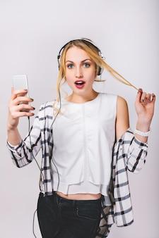Attraktive junge blonde frau mit großen weißen kopfhörern, die musik auf smartphone hören. süßes mädchen, das ihre haare berührt. überraschte große blaue augen, geöffneter mund. isoliert.