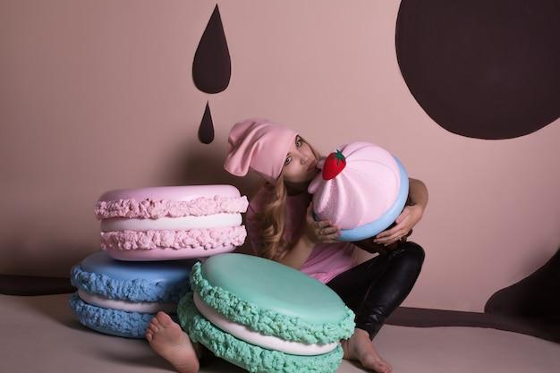 Attraktive junge blonde frau mit rosa t-shirt und mütze, posiert mit großen cupcakes und makronen süßer dekoration