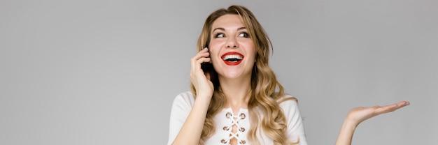 Attraktive junge blonde geschäftsfrau in der lächelnden unterhaltung der schwarzweiss-kleidung