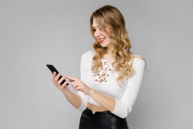 Attraktive junge blonde geschäftsfrau in der schwarzweiss-kleidung lächelnd, handy halten