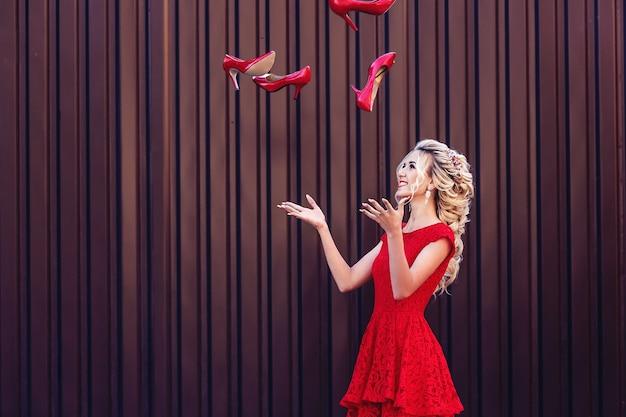 Attraktive junge blondine in einem roten kleid wirft rote schuhe hoch. das konzept von einkauf und verkauf