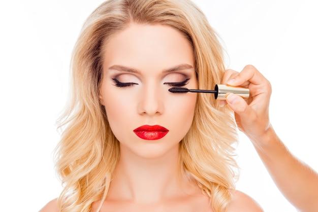 Attraktive junge blondine mit roten lippen, die bürste der wimperntusche halten