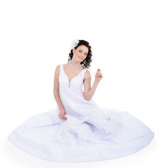 Attraktive junge braut, die auf boden sitzt, gekleidet auf weißem hochzeitskleid