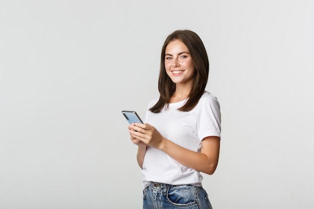 Attraktive junge brünette frau, die handy verwendet und in die kamera lächelt.