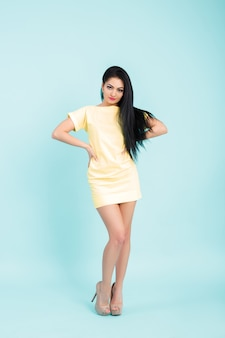 Attraktive junge brünette frau im gelben kleid auf blau