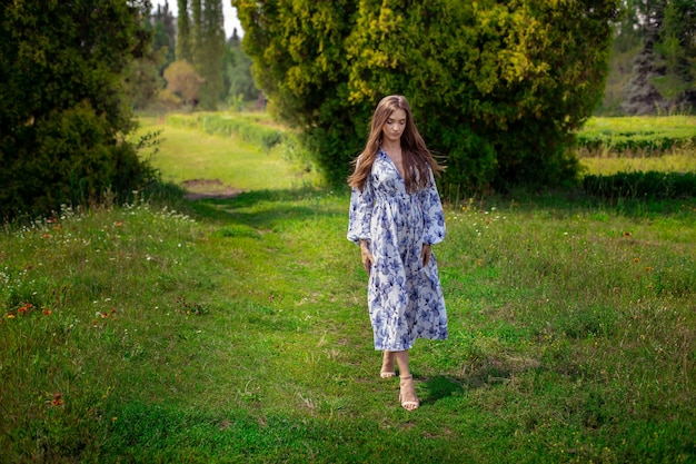 Attraktive junge brünette frau im langen kleid mit blauem blumendruck geht im grünen park spazieren