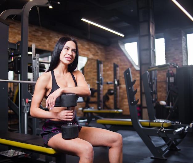 Attraktive junge brünette frau in der sportbekleidung mit einer hantel in ihrer hand, die auf einer bank im fitnessstudio sitzt