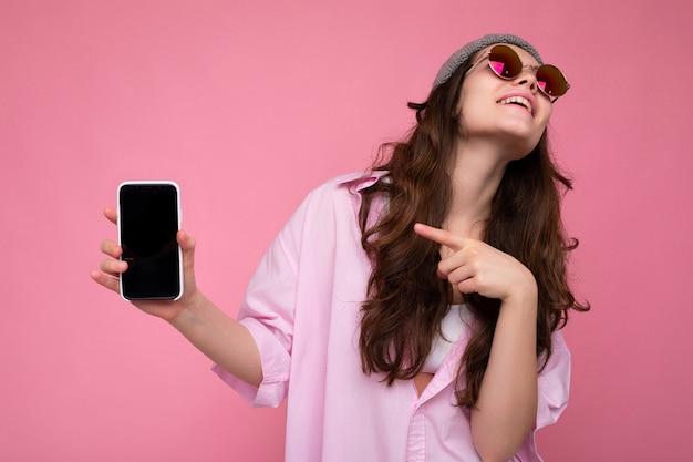 Attraktive junge brünette frau mit stilvollem rosa hemd, grauem hut und bunter sonnenbrille