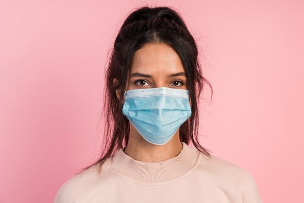 Attraktive junge brünette trägt isoliert eine schutzmaske.