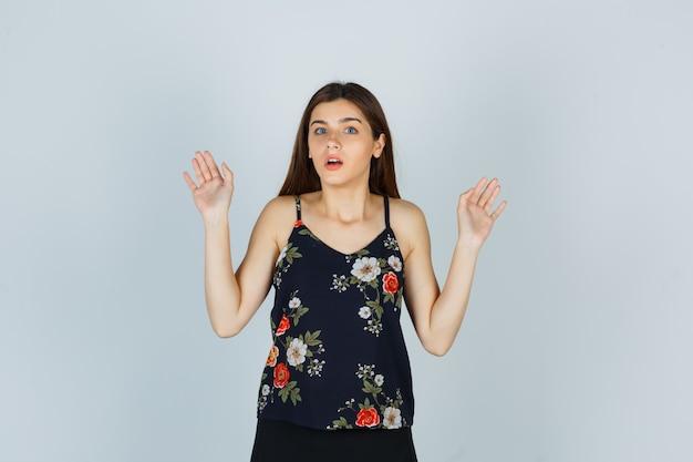 Attraktive junge dame, die kapitulationsgeste in bluse zeigt und verängstigt aussieht, vorderansicht.